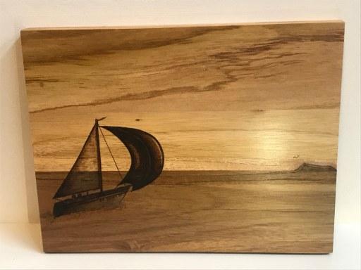 Schilderij van zeilboot op zee bij ondergaande zon. Gepyrografeerd (houtbranden, brandschilderen) op afromosia teak hout.
